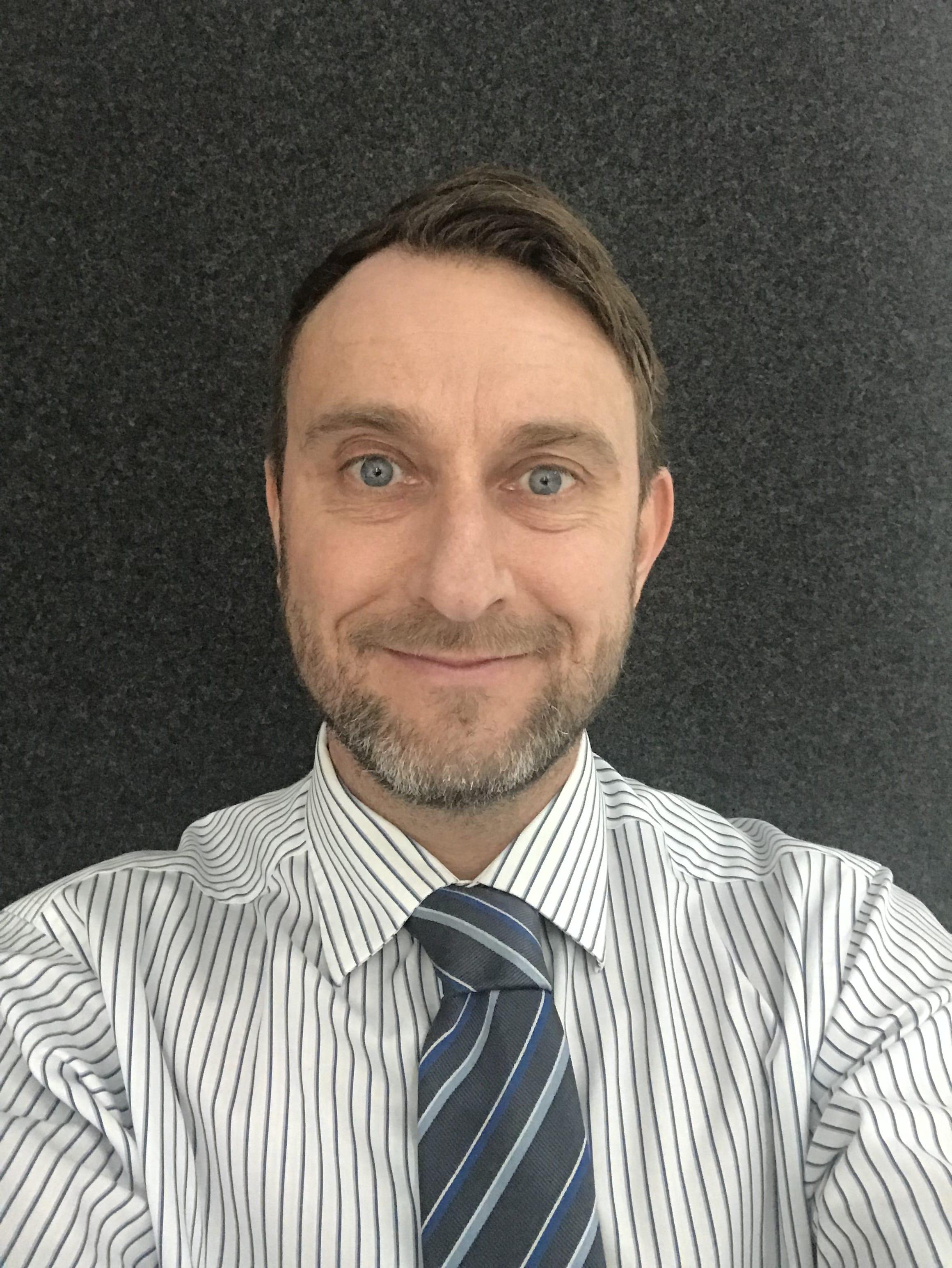 Adam Bradley wearing a striped shirt and tie in a selfie