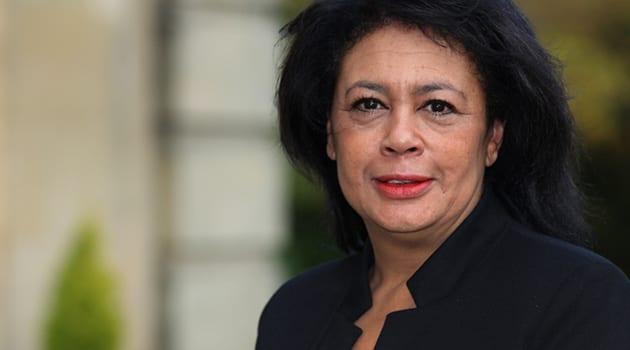 Carmen Watson in a black jacket looks at the camera