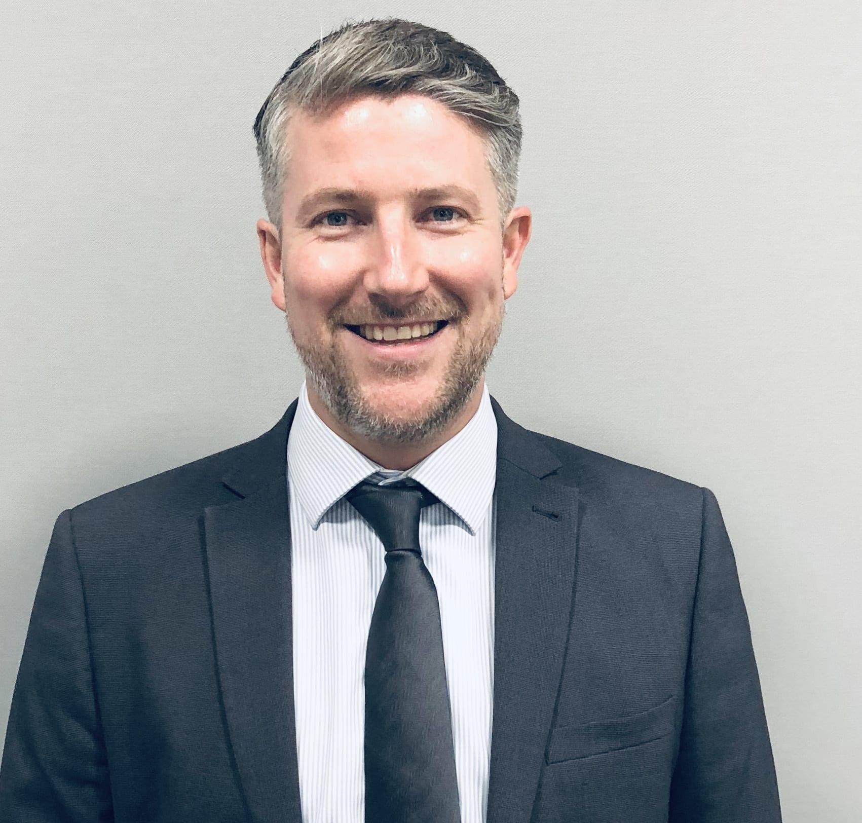 Matt Williams in a suit, smiling