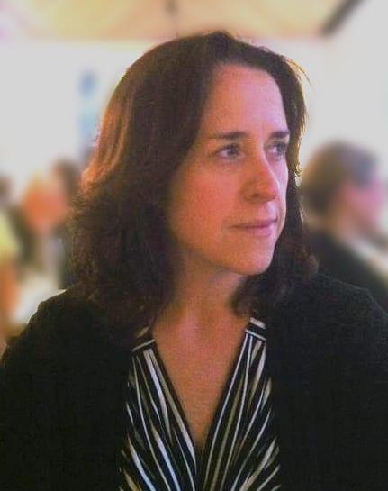 Teresa Brosnan smiles wearing a black-and-white top
