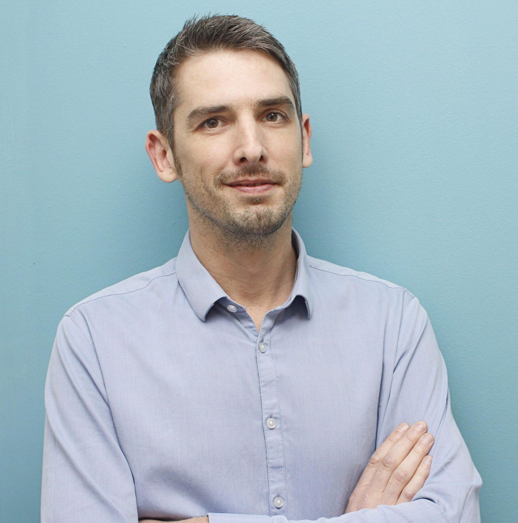 David Lockie smiles with arms folded