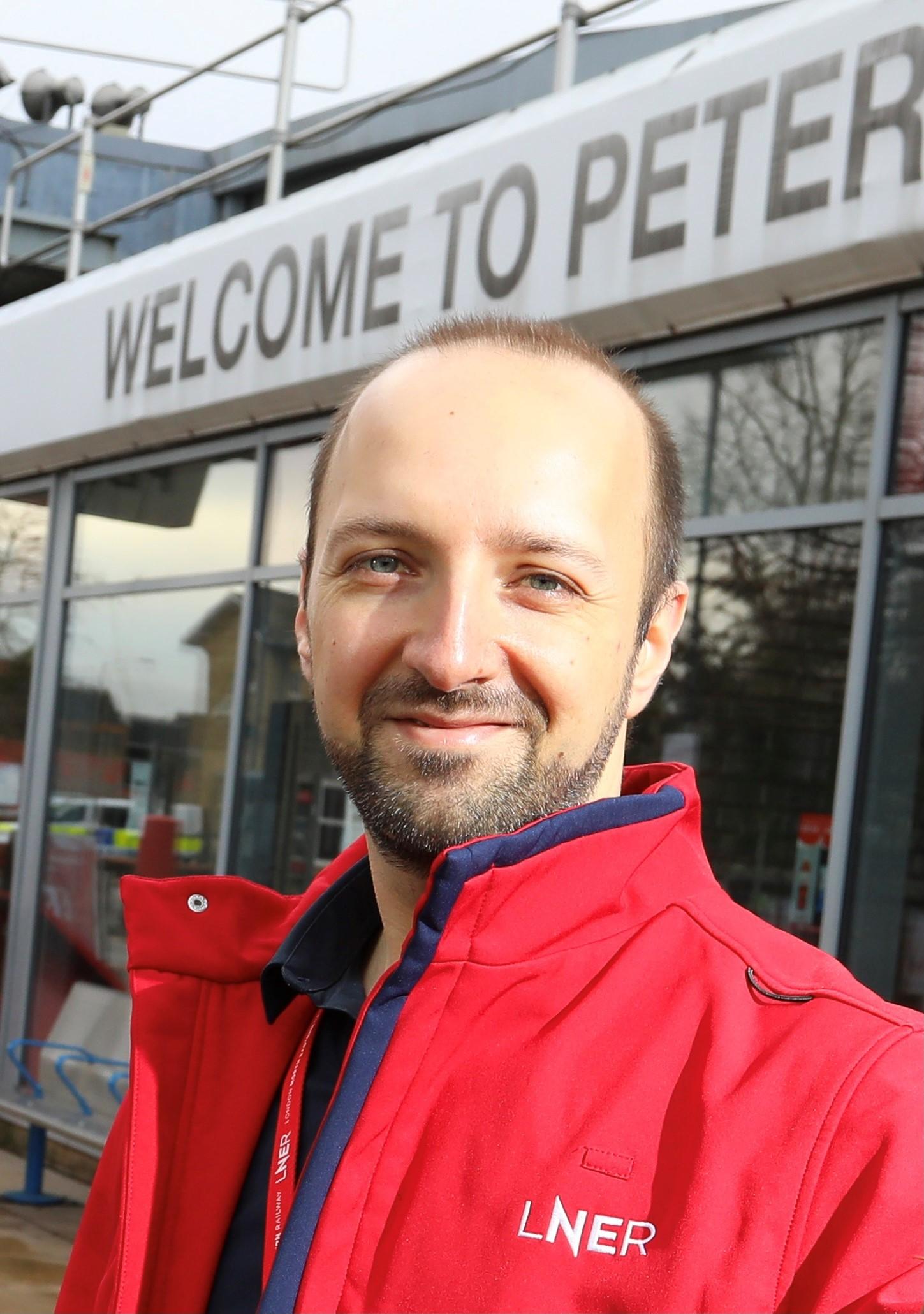 Anthony PateyJohns wearing a red LNER branded jacket stands on a railway station platform.