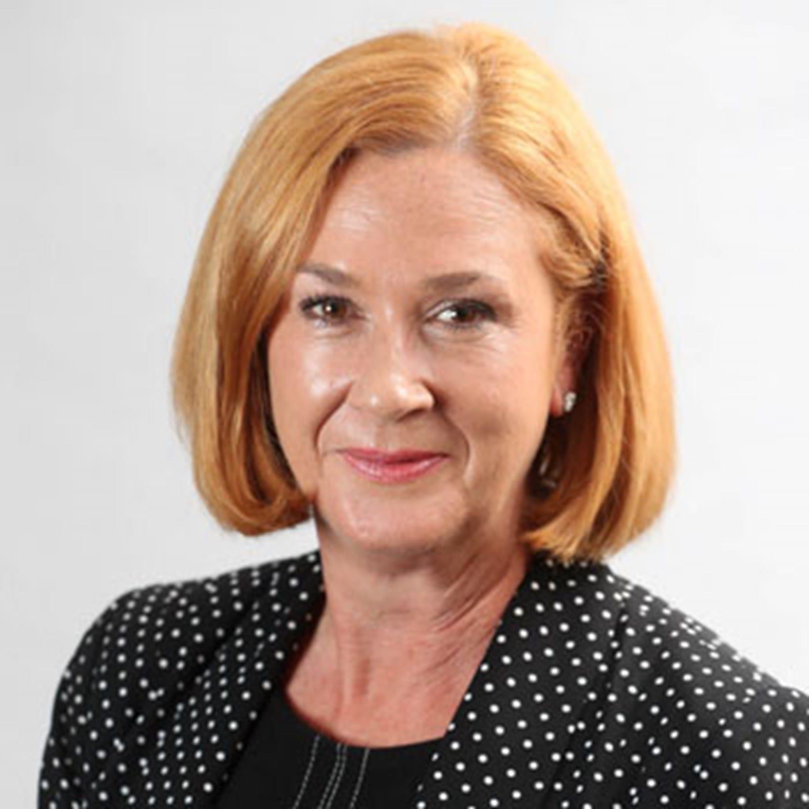Lynn Sheehy in polka dot jacket smiling