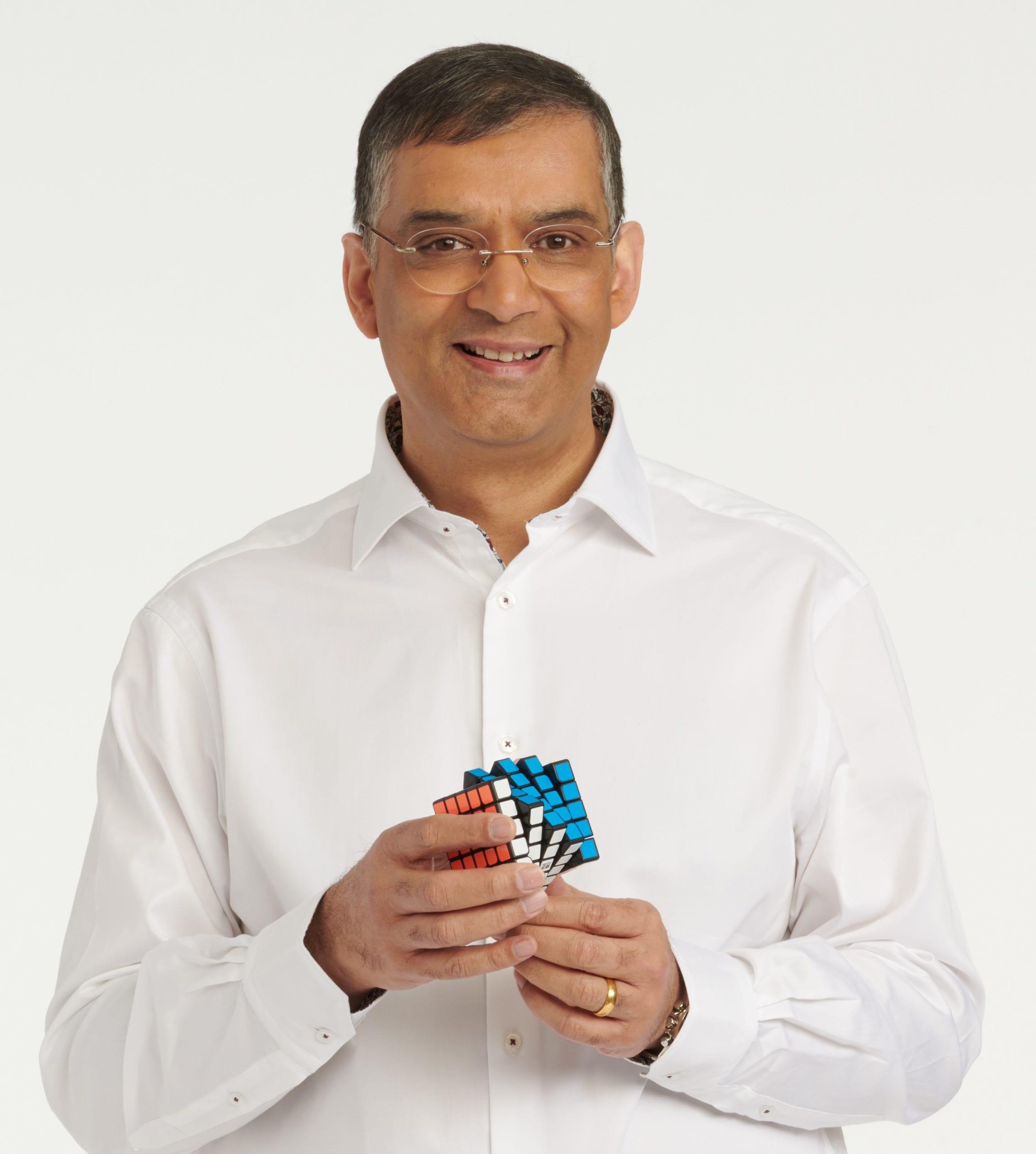Rashik Parmar stands holding a Rubik's cube