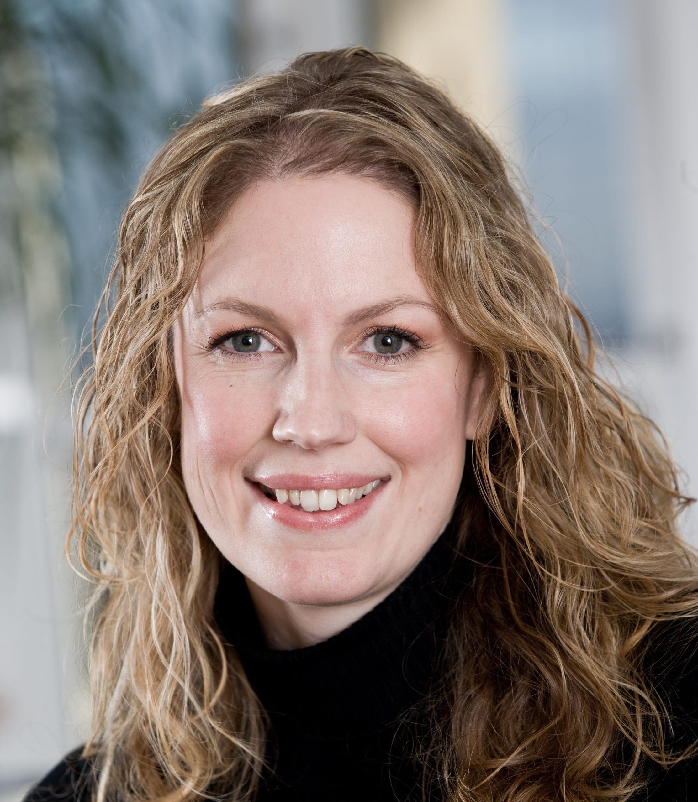 Julie Taylor in a black jumper smiles