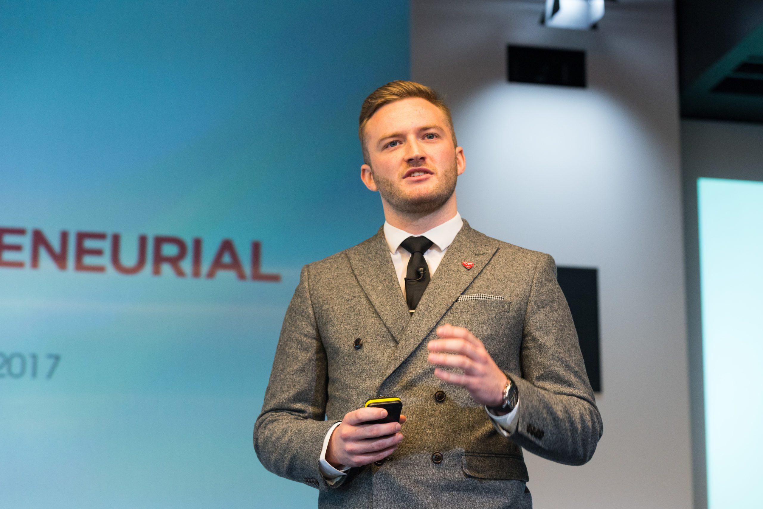 Kris Bryson mid-presentation on a stage