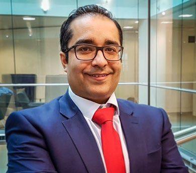 Deepak Soni wearing a suit, smiles into camera